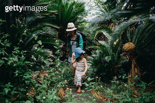 Mother and child hiking in jungle of Sago palm trees, Japan - gettyimageskorea