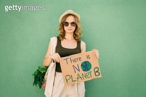 Beautiful blonde girl holding THERE IS NO PLANET B over green background - gettyimageskorea