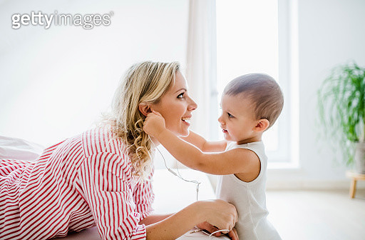 Smiling mother and toddler son using earphones in bedroom at home - gettyimageskorea