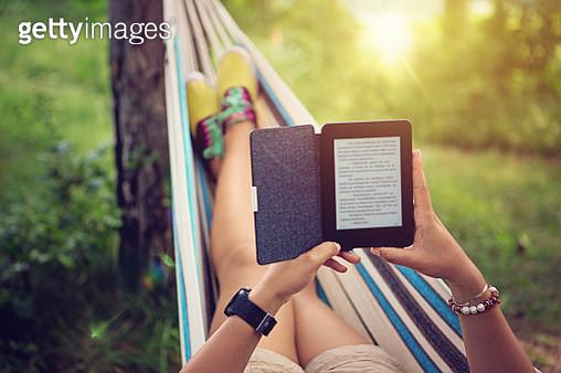 Beautiful girl is reading e-book in the hammock - gettyimageskorea