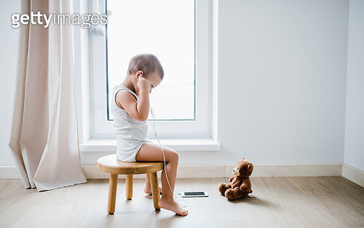 Toddler boy sitting on stool at home using smartphone and earphones - gettyimageskorea