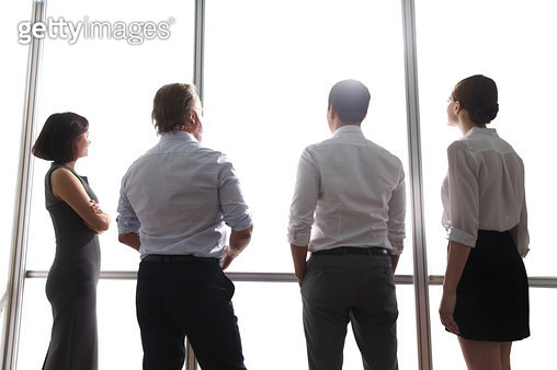 Business people standing in front of the glass window - gettyimageskorea
