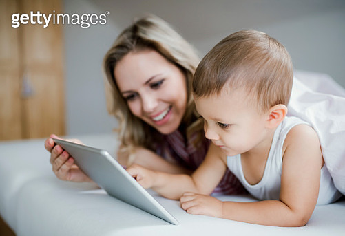 Smiling mother and toddler son lying in bed at home using tablet - gettyimageskorea