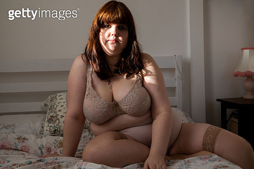 A portrait of a young woman sat on her bed in lingerie looking at the camera - gettyimageskorea