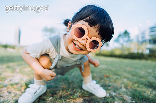 Happy little Asian toddler girl with flower-shaped sunglasses smiling joyfully having fun outdoors enjoying Summer days in the park - gettyimageskorea