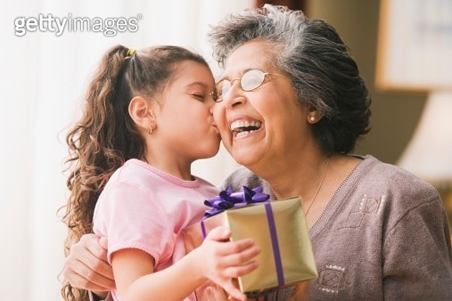 Hispanic granddaughter kissing grandmother and holding gift - gettyimageskorea