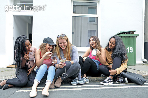 Students relaxing outside house - gettyimageskorea