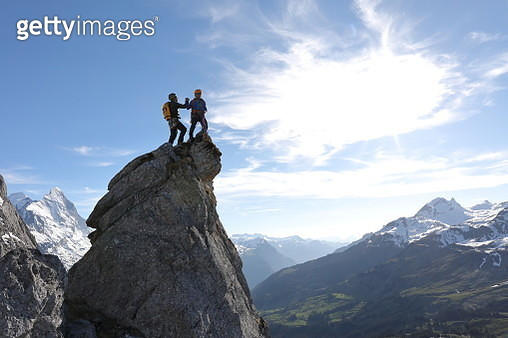Mountaineers scale pinnacle above valley, mtns - gettyimageskorea