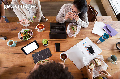 Creative business people working and having lunch in office - gettyimageskorea