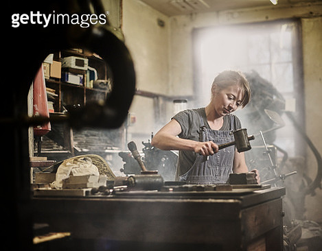 Female printer working in traditional letterpress factory printing using stamps and mallet. - gettyimageskorea