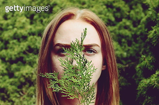 Portrait Of Young Woman Covering Face With Plant Against Trees - gettyimageskorea