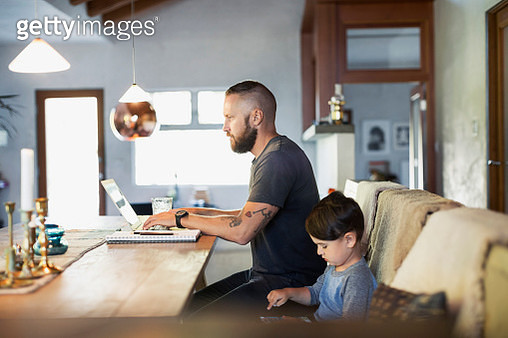 Side view of father and son using technologies at dining table - gettyimageskorea