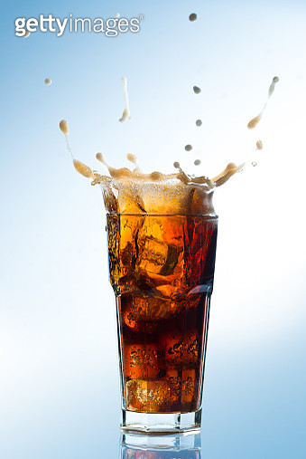 Close-Up Of Drink Splashing In Glass Against Blue Background - gettyimageskorea