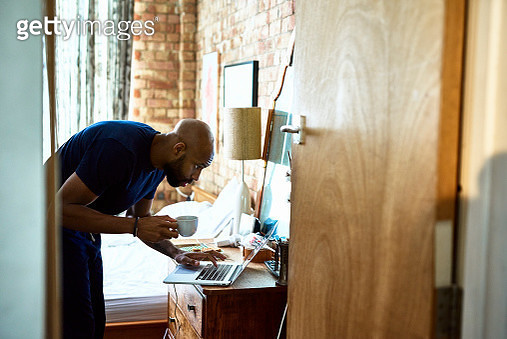Mid adult man using computer on dressing table in hotel room, holding mug, having breakfast whilst getting ready for work - gettyimageskorea