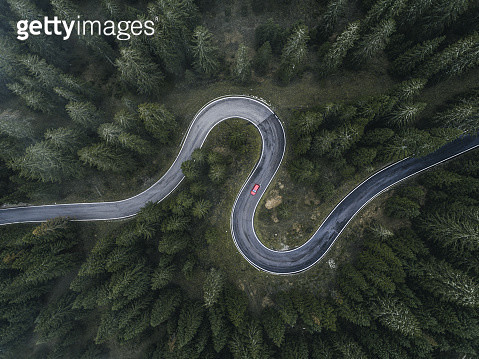 Winding forest road seen and a car shot by drone, Dolomites, Italy - gettyimageskorea