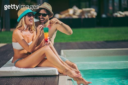 Happy couple by the poolside enjoying in summer cocktail - gettyimageskorea