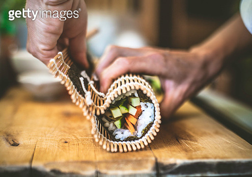Part of a series of images showing sushi made by hand at home using a bamboo mat, fresh and cooked ingredients, and nori seaweed sheets. - gettyimageskorea
