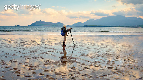 Woman Photographing at Smerwick Harbor during a wonderful sunrise. - gettyimageskorea