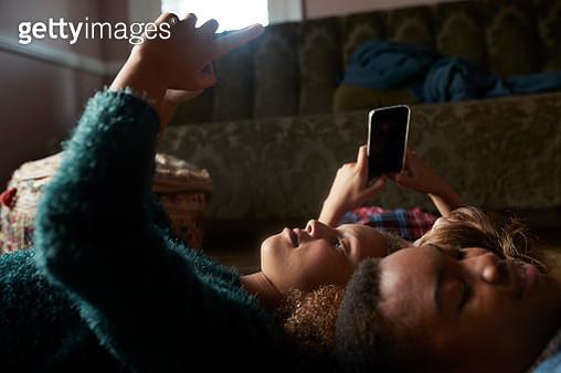 3 tween girls looking at their smartphones - gettyimageskorea