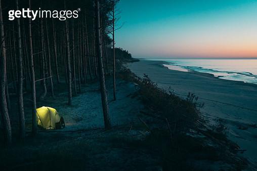 Man on a trip. Glowing tent - gettyimageskorea