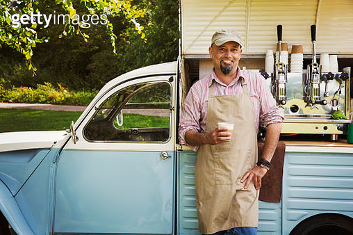 Bearded man wearing apron standing by blue mobile coffee shop, holding hot drink, smiling at camera. - gettyimageskorea