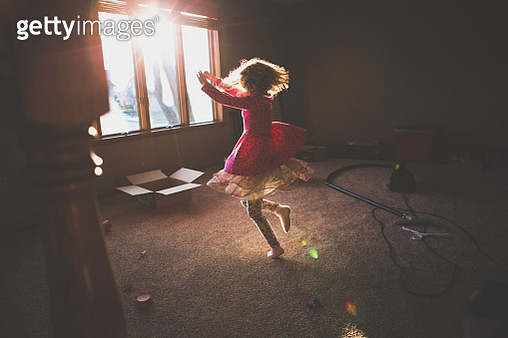 Little girl spins around in an almost empty room and dances in the sunlight. - gettyimageskorea