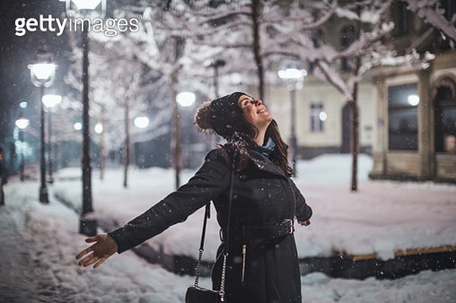 Young woman with arms outstretched in snow - gettyimageskorea