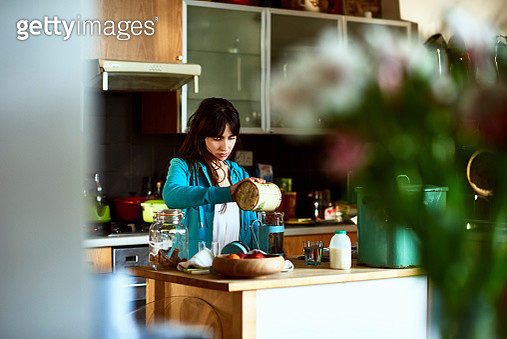 Woman in her 20s at home, preparing breakfast in the morning, concentrating and pouring coffee in casual hooded top - gettyimageskorea