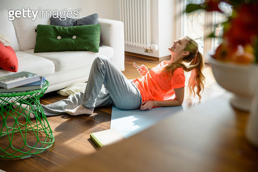 Young woman holding smartphone whilst lounging on floor - gettyimageskorea