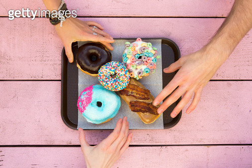 Three hands reaching in for an assortment of colorful doughnuts. - gettyimageskorea