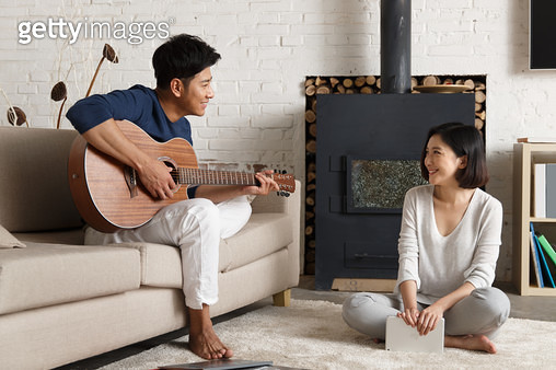 Young couple playing guitar - gettyimageskorea
