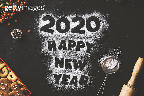 Happy New Year 2020 concept table top flat lay with powdered sugar and cookies. Pine cones , firethorn branches and gingerbread cookies on black background. - gettyimageskorea