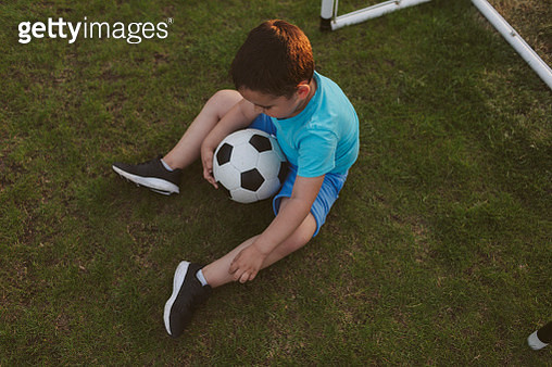 Cute little boy sitting in front of goal on the grass and holding ball. - gettyimageskorea
