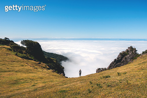 Woman standing on the mountain pasture above the fog, Paul da Serra plateau, Madeira. - gettyimageskorea