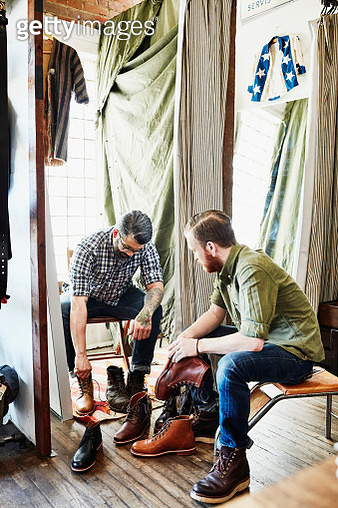 Shop owner helping customer try on boots in mens boutique - gettyimageskorea