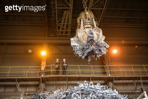 Low angle view of workers watching scrap metal grab in steel foundry - gettyimageskorea