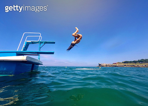 Teenager jumping giving tumbling from a trampoline on the sea - gettyimageskorea