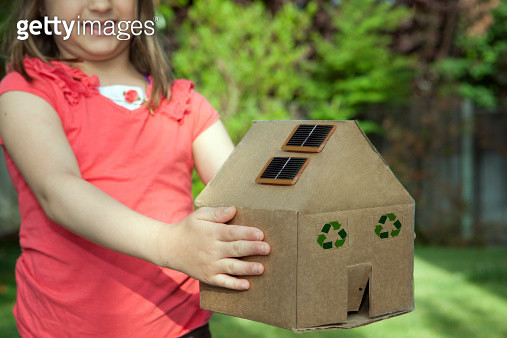 Girl holding a cardboard house with solar panels - gettyimageskorea