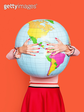 Large inflatable globe getting hugged by a woman in a red skirt. - gettyimageskorea