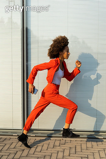 Running young woman with smartphone wearing fashionable red pantsuit - gettyimageskorea