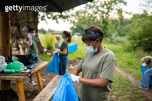 Volunteers wearing protective face masks, cleaning public park during covid-19 pandemic - gettyimageskorea