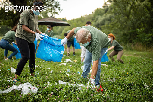 Volunteers picking up garbage while cleaning public park during covid-19 pandemic - gettyimageskorea