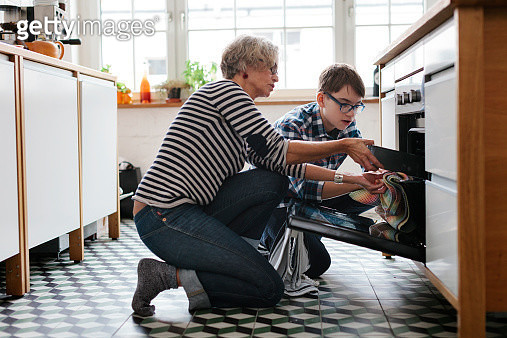 Mature Mother teaching her teenage Son how to make bread. - gettyimageskorea