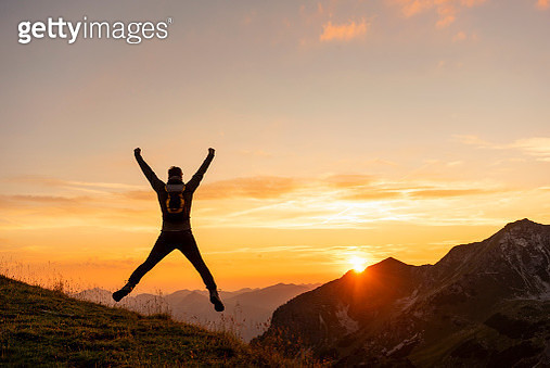 Germany, Bavaria, Oberstdorf, man on a hike in the mountains jumping at sunset - gettyimageskorea