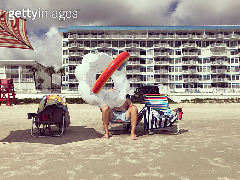 Humorous portrait of a man trying to blow up a giant rainbow cloud inner tube at the beach. Vacation. - gettyimageskorea