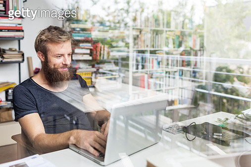 Young bearded man sitting on desk in his home office and working on laptop. - gettyimageskorea
