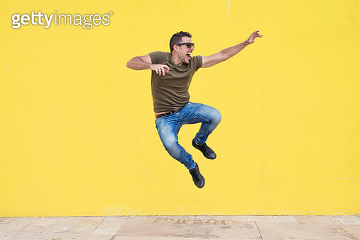 Full Length Of Man Jumping Against Yellow Wall - gettyimageskorea