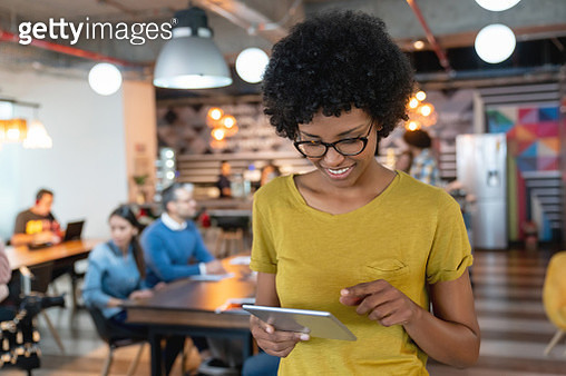 Beautiful black professional woman at a cowroking space looking at a digital tablet smiling - gettyimageskorea