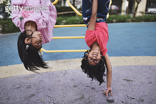 Girl upside down on the jungle gym - gettyimageskorea