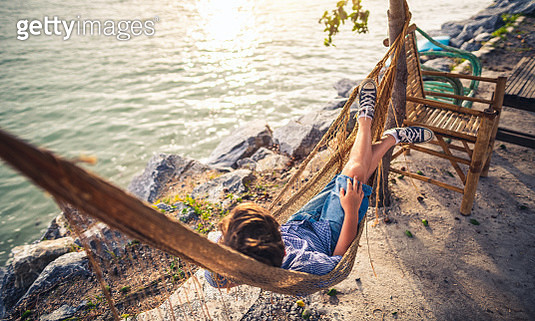 Watching sunset and relaxing in hammock near sea - gettyimageskorea